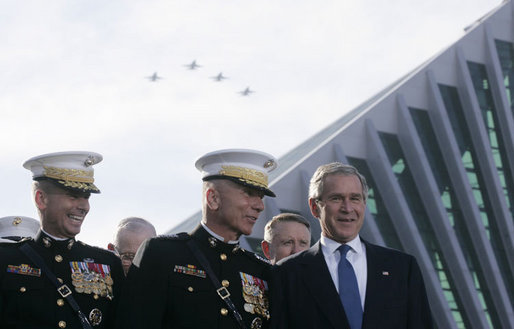 President George W. Bush talks with Chairman of the Joint Chiefs of Staff General Peter Pace, left, and Commandant of the Marine Corps, General Michael Hagee, as a fly over approaches at the dedication ceremony of the National Museum of the Marine Corps Friday, Nov. 10, 2006, in Quantico, Va. White House photo by Paul Morse