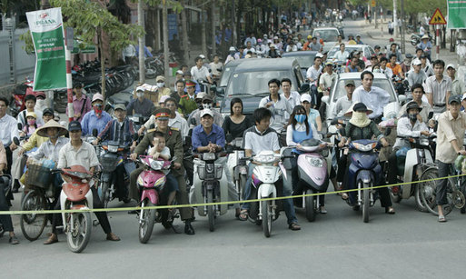 Pedestrians and cyclists line the motorcade route in Hanoi as President George W. Bush and Mrs. Laura Bush head to the Sheraton Hanoi Hotel Friday, Nov. 17, 2006, after their arrival in Vietnam. White House photo by Paul Morse