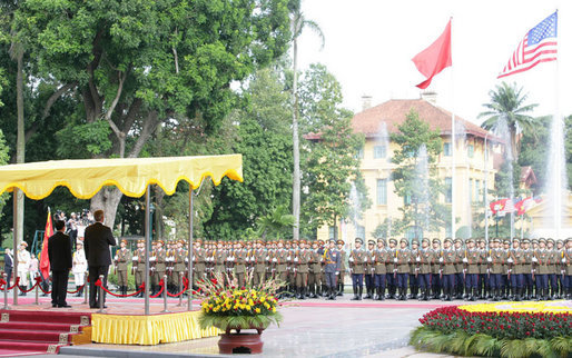 President George W. Bush and President Nguyen Minh Triet of Vietnam, stand at attention during the playing of the national anthems Friday, Nov. 17, 2006, during the arrival ceremony for the President and Mrs. Bush at the Presidential Palace in Hanoi. White House photo by Shealah Craighead