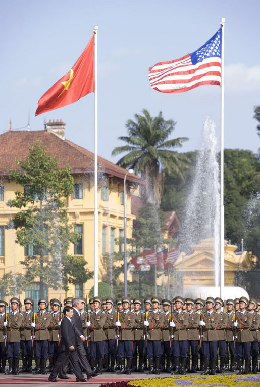 Under the American and Viet flags, President George W. Bush and President Nguyen Minh Triet review the honor guard during the arrival ceremony Friday, Nov. 17, 2006, in Hanoi. White House photo by Shealah Craighead