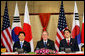 President George W. Bush sits with President Roh Moo-Hyun, of the Republic of Korea, left, and Japan's Prime Minister Shinzo Abe during a trilateral discussion Saturday, Nov. 18, 2006, at the Sheraton Hanoi hotel in Hanoi, where they are participating in the Asian Pacific Economic Cooperation summit. White House photo by Eric Draper