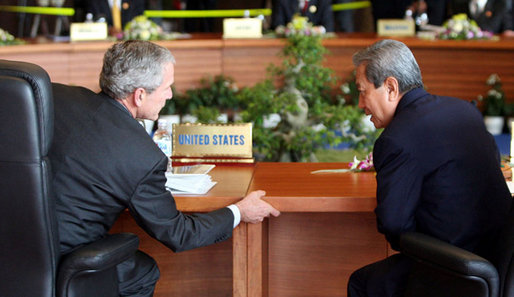 President Bush leans in to talk with Prime Minister Surayud Chulanont of Thailand during the first retreat of APEC leaders Saturday, Nov. 18, 2006, at the National Conference Center in Hanoi. White House photo by Eric Draper