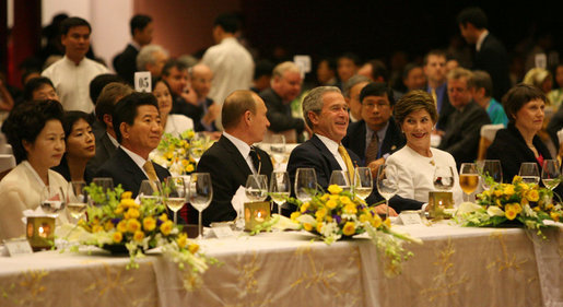 President George W. Bush and Mrs. Laura Bush enjoy the APEC gala dinner and cultural performance Saturday, Nov. 18, 2006, at the National Convention Center in Hanoi. They are seated with President Vladimir Putin of Russia, and President Roh Moo-hyun of the Republic of Korea, left, and Prime Minister Helen Clark of New Zealand, right. White House photo by Eric Draper