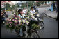Vendors on mopeds carry flowers for sale early Saturday morning, Nov. 18, 2006, in Hanoi. White House photo by Paul Morse