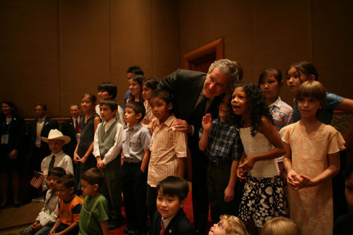 President George W. Bush joins kids of U.S. Embassy staff for a photo at the Sheraton Hanoi Saturday, Nov. 18, 2006. White House photo by Paul Morse