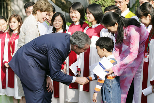 President George W. Bush and Mrs. Laura Bush pause to greet a young boy as they leave church services Sunday, Nov. 19, 2006, at the Cua Bac Church in Hanoi. White House photo by Shealah Craighead