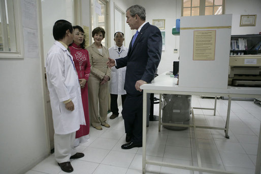 President George W. Bush and Mrs. Laura Bush are briefed as they tour the Pasteur Institute in Ho Chi Minh City Monday, Nov. 20, 2006.