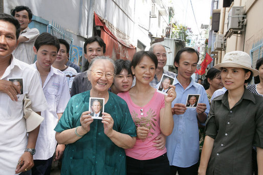 Onlookers line the street of Ho Chi Minh City Monday, Nov. 20, 2006, holding pictures of President George W. Bush, who was joined by Mrs. Laura Bush for a daylong visit to the city. White House photo by Shealah Craighead