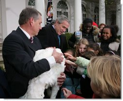 "President George W. Bush invites children to meet ""Flyer"" the turkey, held by Lynn Nutt of Springfield, Mo., during a ceremony Wednesday, Nov. 22, 2006 in the White House Rose Garden, following the President's pardoning of the turkey before the Thanksgiving holiday. White House photo by Paul Morse"