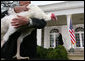 "President George W. Bush waves farewell to invited guests as a grateful ""Flyer"" the turkey watches Wednesday, Nov. 22, 2006 from the White House Rose Garden, following the President's pardoning of the turkey before the Thanksgiving holiday. White House photo by Paul Morse"