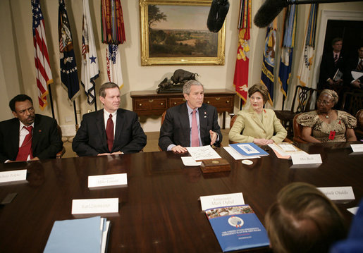 President George W. Bush talks with reporters at a meeting hosted by President Bush and Laura Bush on World AIDS Day in the Roosevelt Room at the White House, Friday, Dec. 1, 2006. President Bush said the United States is committed in helping solve this problem by dedicating a lot of resources to battle against HIV/AIDS around the world. President Bush is seen with, from left to right, Dr. Getachew Feleke of the Nassau U. Medical Center of Farmingdale, N.Y.; U.S. Secretary of Health and Human Resources, Michael O. Leavitt and Angelina Magaga, right, of the Light and Courage Center Trust of Botswana, Africa. White House photo by Eric Draper