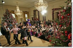 "President George W. Bush and Mrs. Laura Bush sit with children of deployed U.S. military personnel and watch a performance of ""Willy Wonka"" by members of The Kennedy Center Education Department in the East Room Monday, Dec. 4, 2006. White House photo by Eric Draper"