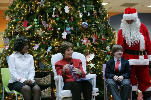 Mrs. Laura Bush sits with patient escorts Allison Meads, left, and Matthew Morgan, as she reads to an audience of children, patients and hospital staff Friday, Dec. 8, 2006, at The Children's National Medical Center in Washington, D.C., where Mrs. Bush visited with patients and debuted the 2006 Barney Cam video. White House photo by Shealah Craighead