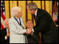 "President George W. Bush congratulates Ruth Johnson Colvin after presenting her with the Presidential Medal of Freedom Friday, Dec. 15, 2006, in the East Room of the White House. Said the President, ""Ruth Colvin is a person of intelligence and vision and heart. And she has earned the gratitude of many, and the admiration of us all."" White House photo by Eric Draper"
