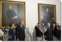 President George W. Bush and Laura Bush watch as Ariel Cohen, 14, lights the Menorah on the fourth night of Hanukkah during the annual White House Hanukkah reception Monday, Dec. 18, 2006. Pictured at right are Ariel's parents, Dan and Rachel Cohen, and sister Alison, 11.  White House photo by Shealah Craighead