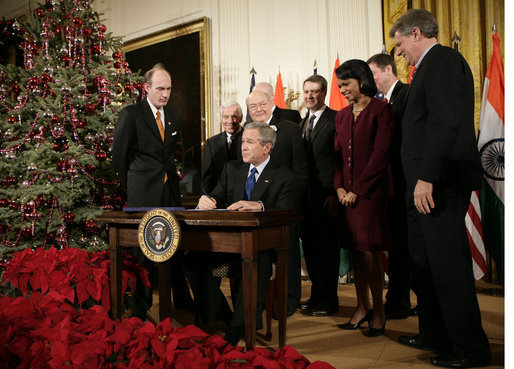 President George W. Bush is joined by U.S. Secretary of State Condoleezza Rice and U.S. legislators, as he signs H.R. 5682 The United States-India Peaceful Atomic Cooperation Act, Monday, Dec. 18, 2006, in the East Room of the White House. H.R. 5682 will allow the U.S. and India to share civilian nuclear technology and bring India's civilian nuclear program under the safeguards of the International Atomic Energy Agency. White House photo by Eric Draper