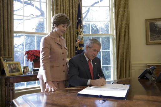 Laura Bush stands by President George W. Bush as he signs H.R. 6143, the Ryan White HIV/AIDS Treatment Modernization Act of 2006, in the Oval Office Tuesday, Dec. 19, 2006. White House photo by Eric Draper