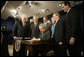 President George W. Bush signs H.R. 6111, the Tax Relief and Health Care Act of 2006, in the Dwight D. Eisenhower Executive Office Building, Dec. 20, 2006. Pictured with the President are, from left: Speaker Dennis Hastert, Sen. Bill Frist, R-Tenn., obscured, Sen. Pete Domenici, R-N.M., obscured, Rep. Bill Thomas, R-Calif., Sen. David Vitter, R-La., Secretary of the Interior, Dirk Kempthorne, obscured, Sen. Mary Landrieu, D-La., Sen. Mike DeWine, R-Ohio and Sen. Rick Santorum, R-Pa. White House photo by Kimberlee Hewitt