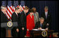 President George W. Bush signs H.R. 6407, the Postal Accountability and Enhancement Act, Wednesday, Dec. 20, 2006, at the Eisenhower Executive Office Building in Washington, D.C., joined by, from left to right, Postmaster General Jack Potter, Sen. Thomas Carper of Delaware, James C. Miller III, Chairman of the Postal Service Board of Governors; Rep. Tom Davis of Virginia, Sen. Susan Collins of Maine, Rep. Danny Davis of Illinois and Rep. John McHugh of New York. White House photo by Eric Draper