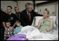 President George W. Bush congratulates Army Specialist Sue Downes after presenting the Iowa City, Iowa soldier with a Purple Heart Friday, Dec. 22, 2006, at the Walter Reed Army Medical Center where she is recovering from injuries suffered in Operation Iraqi Freedom. Joining in the presentation is Pvt. Downes' husband, Gabriel, their son Austin and daughter Alexis, and mother, Faye Partin. White House photo by Eric Draper