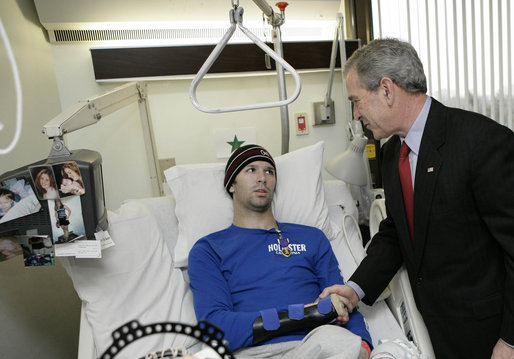 President George W. Bush congratulates U.S. Army Pvt. First Class Jace Badia of Tampa, after presenting him with a Purple Heart Friday, Dec. 22, 2006, during a visit to Walter Reed Army Medical Center where the soldier is recovering from injuries suffered in Operation Iraqi Freedom. White House photo by Eric Draper
