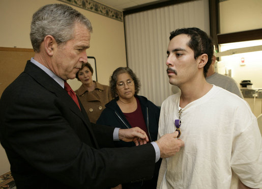 President George W. Bush presents the Purple Heart to U.S. Army Staff Sgt. Robert Cordero of El Paso, during a visit Friday, Dec. 22, 2006, to the Walter Reed Army Medical Center where the soldier is recovering from injuries suffered in Operation Iraqi Freedom. Looking on with Mrs. Laura Bush is Sgt. Cordero's mother, Rosa. White House photo by Eric Draper