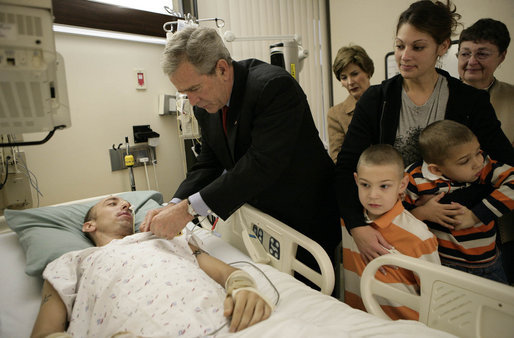 President George W. Bush presents a Purple Heart to Sgt. John Kriesel of Twin Cities, Minn., during a visit Friday, Dec. 22, 2006, to Walter Reed Army Medical Center where the National Guardsman is recovering from injuries suffered in Operation Iraqi Freedom. Looking on with Mrs. Laura Bush is Sgt. Kriesel's wife, Katie, holding their 4-year-old son Broden and 5-year-old son Elijah. White House photo by Eric Draper