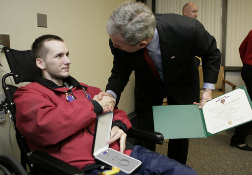 President George W. Bush congratulates Pvt. First Class Tony Brawdy of Tulsa, OK., after presenting him with two Purple Hearts Friday, Dec. 22, 2006, during a visit to Walter Reed Army Medical Center, where the soldier is recovering from injuries suffered in Operation Iraqi Freedom. White House photo by Eric Draper