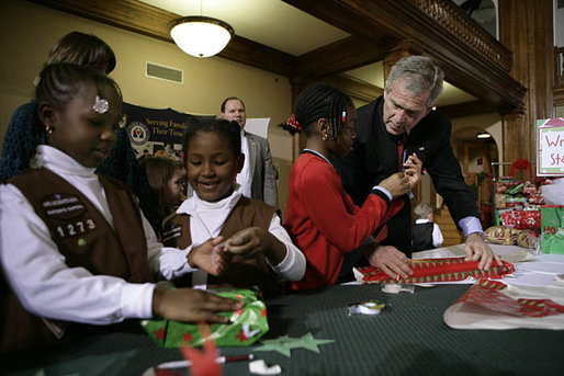 President George W. Bush helps young volunteers wrap presents for families of soldiers who were wounded in Iraq and Afghanistan, Friday, Dec. 22, 2006, at Walter Reed Army Medical Center in Washington, D.C. White House photo by Eric Draper