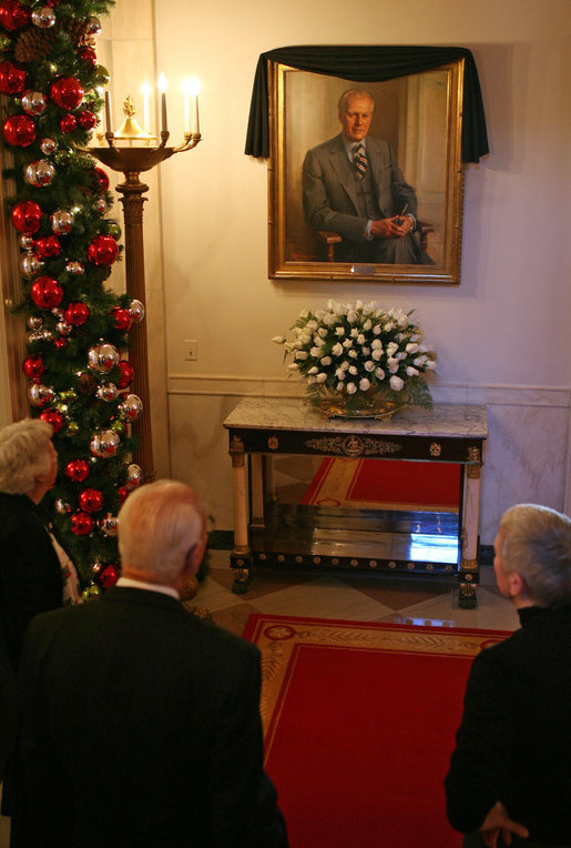 Visitors to the White House look at the portrait of former President Gerald R. Ford is draped with a black cloth in the Cross Hall of the White House Wednesday, Dec. 27, 2006. President Ford passed away Tuesday evening, Dec. 26. The portrait was painted by artist Everett Raymond Kinstler in 1977.
