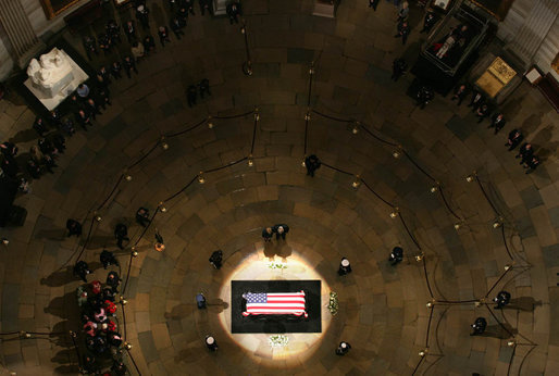 President George W. Bush and Mrs. Laura Bush stand at the side of his flag-draped coffin as they pay their respects to the late President Gerald R. Ford Monday, Jan. 1, 2007, in the Rotunda of the U.S. Capitol. White House photo by Shealah Craighead