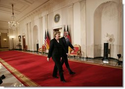 President George W. Bush and German Chancellor Angela Merkel leave Cross Hall at the White House, Thursday evening, Jan. 4, 2006, following their joint news conference.  White House photo by Eric Draper