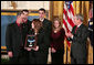 "President George W. Bush presents the Medal of Honor to the family of Corporal Jason Dunham of the Marine Corps during a ceremony in the East Room Thursday, Jan. 11, 2007. The President spoke of Cpl. Dunham, ""In April 2004, during an attack near Iraq's Syrian border, Corporal Dunham was assaulted by an insurgent who jumped out of a vehicle that was about to be searched. As Corporal Dunham wrestled the man to the ground, the insurgent rolled out a grenade he had been hiding. Corporal Dunham did not hesitate. He jumped on the grenade, using his helmet and body to absorb the blast. Although he survived the initial explosion, he did not survive his wounds. But by his selflessness, Corporal Dunham saved the lives of two of his men, and showed the world what it means to be a Marine.""  White House photo by Paul Morse"