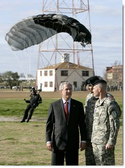 President George W. Bush speaks with U.S. Army Colonel Mike Linnington, center, and Sgt. 1st Class Mike Hertig, right, as he watches paratroopers from the U.S. Army Silver Wings Command exhibition team land Thursday, Jan. 11, 2006, during a demonstration of airborne infantry training at Fort Benning, Ga. White House photo by Eric Draper