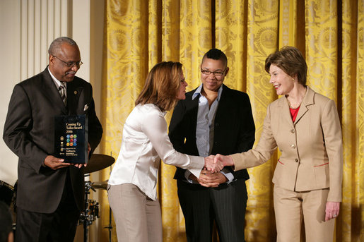Mrs. Laura Bush presents Michelle Butler, left, and Alisa Lemon, center, of Studioworks, part of Communities in Schools in New Jersey, a Coming Up Taller Award during a ceremony in the East Room Monday, Jan. 22, 2007. James Farmer of PCAH is pictured at the far left. Each year, the Coming Up Taller Awards recognize and reward excellence in community arts and humanities programs for underserved children and youth. White House photo by Shealah Craighead