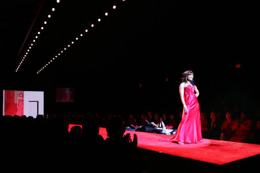Mrs. Laura Bush and Joyce Cullen, a heart disease survivor, watch Angela Bassett model a red dress by Carmen Marc Valvo during the Red Dress Collection Celebrity Fashion Show at Bryant Park in New York, Friday, Feb. 2, 2007. White House photo by Shealah Craighead