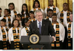 President George W. Bush, standing with members of the Jackson High School Black History Tour Group of Jackson, Mich., welcomes guests to the East Room of the White House, Monday, Feb. 12, 2007, during the celebration of African American History Month.  White House photo by Eric Draper