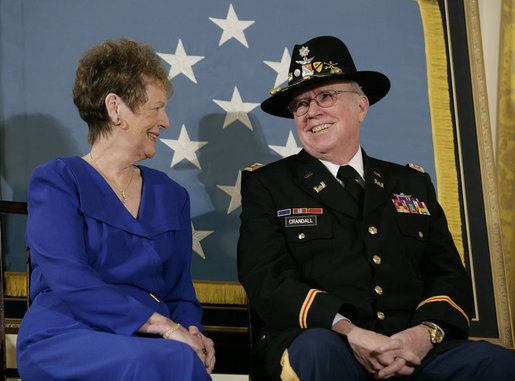 U.S. Army Major Bruce P. Crandall sits with his wife, Arlene, before a banner of the Medal of Honor in the East Room of the White House, Monday, Feb. 26, 2007, prior to Crandall being awarded the Medal of Honor for his extraordinary heroism as a 1st Cavalry helicopter flight commander in the Republic of Vietnam in November 1965. White House photo by Eric Draper