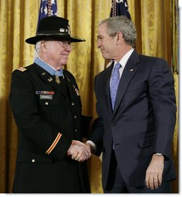 President George W. Bush shakes hands with U.S. Army Major Bruce P. Crandall after awarding Crandall the Medal of Honor in a ceremony in the East Room of the White House, Monday, Feb. 26, 2007, for his extraordinary heroism as a 1st Cavalry helicopter flight commander, completing 22 flights under intense enemy fire to aid troops in the Republic of Vietnam in November 1965. White House photo by Eric Draper