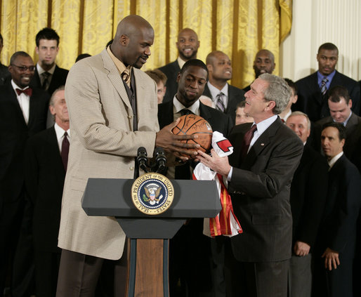 "President George W. Bush receives an autographed ball from Shaquille O'Neal Tuesday, Feb. 27, 2007, as the 2006 NBA champions visited the White House. The President told the East Room audience he was most impressed by the Heat's work in their Miami community and added, ""I mean, I'm in awe of their athletic skills. Standing next to Shaq is an awe-inspiring experience."" White House photo by Eric Draper"