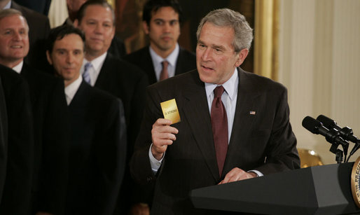 "President George W. Bush holds up a card saying ""15 Strong,"" this year's motto for the 2006 NBA champion Miami Heat, during the team's visit Tuesday, Feb. 27, 2007 to the White House. Said the President, ""They had the stars. but it was the capacity to play together, to put the team ahead of themselves, that enabled them to be here at the White House."" White House photo by Paul Morse"