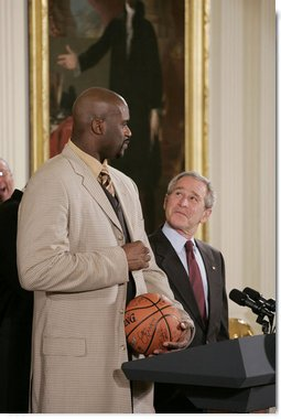 "President George W. Bush looks up as he prepares to receive an autographed ball from Shaquille O'Neal Tuesday, Feb. 27, 2007, as the 2006 NBA champions visited the White House. The President told the East Room audience he was most impressed by the Heat's work in their Miami community and added, ""I mean, I'm in awe of their athletic skills. Standing next to Shaq is an awe-inspiring experience.""  White House photo by Paul Morse"
