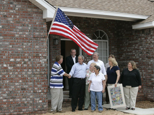 President George W. Bush shakes hands with Ernie Woodward of Long Beach, Miss. after Woodward, joined by his family, raised a flag given to them by President Bush outside his home Thursday, March 1, 2007, during the President's tour of the neighborhood where some homes damaged by Hurricane Katrina have been rebuilt with Gulf Coast grant money. White House photo by Eric Draper
