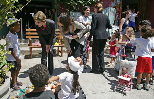 Mrs. Laura Bush talks with a little boy at Projeto Aprendiz Friday, March 9, 2007, in Sao Paolo, Brazil. Developing the concept of the neighborhood as a school, the program supplements school education with a wide range of community-based activities that nurture young people's creativity and self-esteem. White House photo by Shealah Craighead