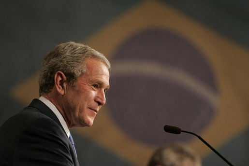 "President George W. Bush smiles as he listens to Brazil President Luiz Inacio Lula da Silva reply to a question Friday, March 9, 2007, during a joint press availability in Sao Paulo. Said President Lula, ""The memorandum of understanding on biofuels, which our ministers signed today, is a decisive step. Bringing together their efforts, the U.S. and Brazil can further push the democratization of energy and bring biofuels to all."" White House photo by Paul Morse"