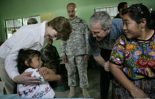 President George W. Bush and Mrs. Laura Bush play with a young girl during a visit Monday, March 12, 2007, to the Carlos Emilio Leonardo School in Santa Cruz Balanya, Guatemala. The couple visited a medical readiness and training exercise site at the school. White House photo by Eric Draper