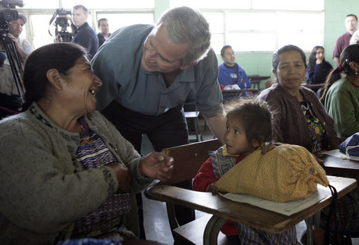 President George W. Bush talks with a woman and young girl Monday, March 12, 2007, during his visit to the Carlos Emilio Leonard School in Santa Cruz Balanya, Guatemala. White House photo by Eric Draper