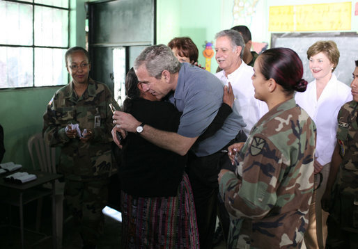 President George W. Bush gets a hug from a woman Monday, March 12, 2007, during a visit to a medical readiness and training exercise site at the Carlos Emilio Leonardo School in Santa Cruz Balanya, Guatemala. Also pictured is Guatemalan President Oscar Berger, center, and Mrs. Laura Bush. White House photo by Paul Morse