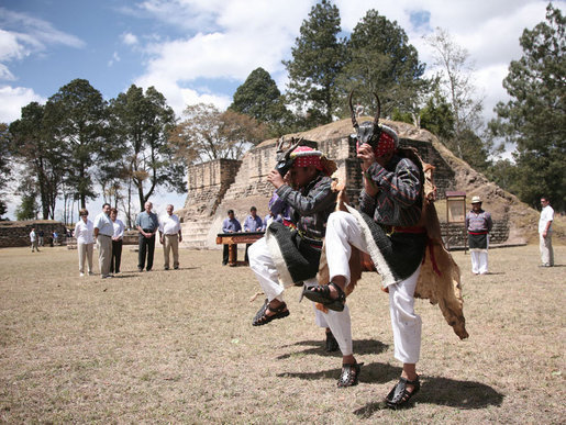 Members of the Patzun Dance group perform a cultural dance Monday, March 12, 2007, during a visit to Iximche, Guatemala, by President George W. Bush and Mrs. Laura Bush and President Oscar Berger of Guatemala and his wife, Mrs. Wendy Widmann de Berger, who look on in the background. White House photo by Paul Morse