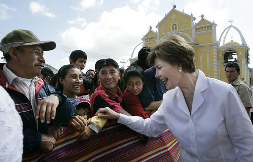Mrs. Laura Bush reaches out to a small child during a visit Monday, March 12, 2007, to the Town Square in Santa Cruz Balanya, Guatemala. White House photo by Eric Draper
